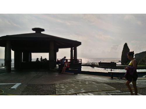 高台の温泉エリア。朝日温泉は、付近の海域の海水や地下水が地底に滲み込んだ後、マグマ溜まりの熱で温められ、それが潮間帯から湧き出たもの。水質は無色透明で、海水のしょっぱさを帯び、さらさらとしている。