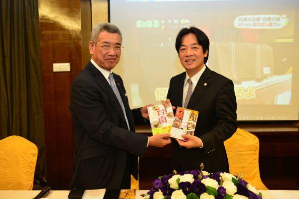 頼清徳市長(右)から市の観光パンフレット「台南帖」を手渡される野口一会長=台南市政府提供