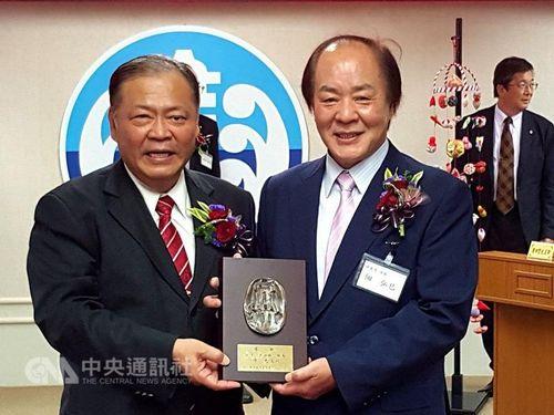 互いに記念品を贈呈する陳光復氏(左)と佃弘巳氏=2015年の訪台時