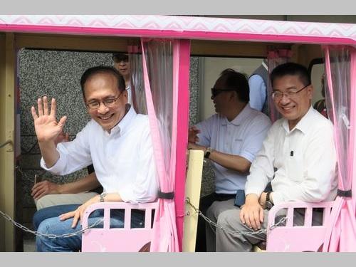 トロッコに乗って報道陣に手を振る林全行政院長(首相、左)