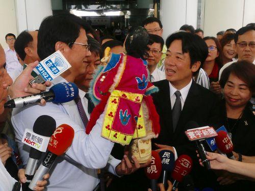 頼清徳次期行政院長(手前右から2人目)をポテヒの人形で見送る謝龍介台南市議(左)
