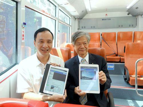 バスに乗って無料のWi-Fiサービスを利用する朱立倫・新北市長(左)=新北市政府提供