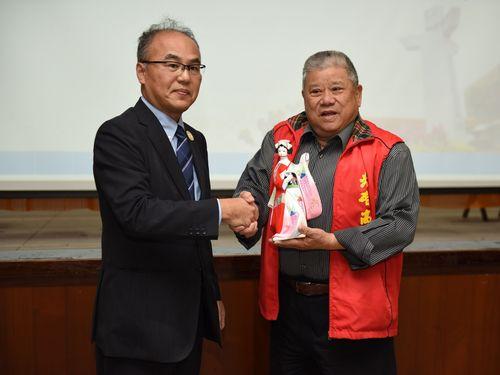 筑紫台高校の代表(左)に記念品を贈られる光啓高校の黄東栄董事長(右)