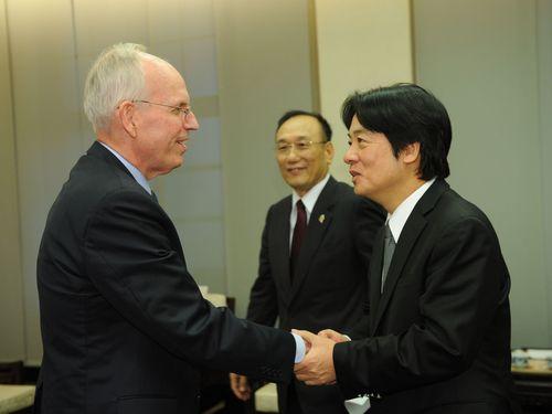 ジョン・ノリス執行理事(左)と握手を交わす頼清徳行政院長