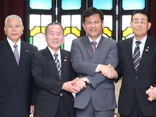 台中市の林佳龍市長(右から2人目)と握手する金沢市議会の黒沢和規議長(同3人目)