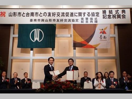 締結式で握手する李孟諺台南市長代理(手前右)と佐藤孝弘山形市長(同左)=台南市政府提供