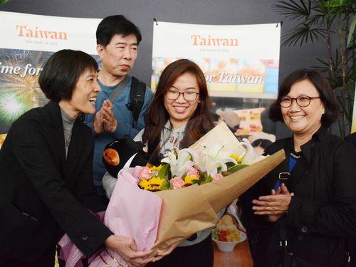 観光局職員から花束を受け取るシンガポール人女性(右から2人目)