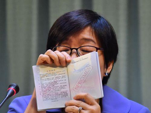 イラストの誤植が見つかった新たな旅券(パスポート)を手に今後の対処について説明を行う外交部領事事務局の蔡幼文副局長