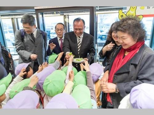 日本の子供たちに台湾ナツメを振る舞う農業委員会の林聡賢主任委員(後列左から3人目)。赤いマフラー姿の女性は陳菊高雄市長=同委提供