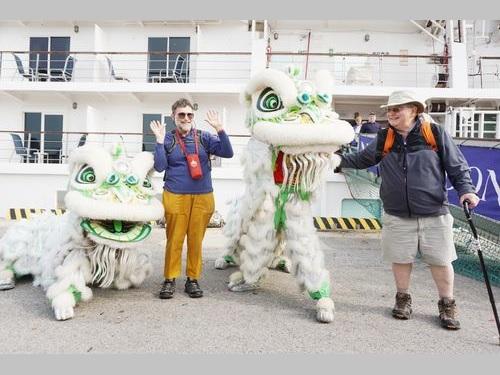 獅子舞の歓迎を受ける欧米からの観光客ら