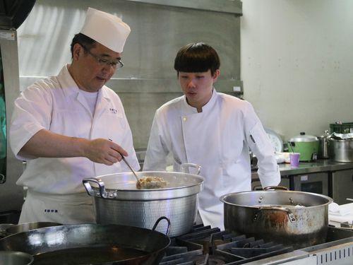 台湾の大学生に料理を指導する服部栄養専門学校の専任講師、一枚田清行さん(左)=弘光科技大学提供