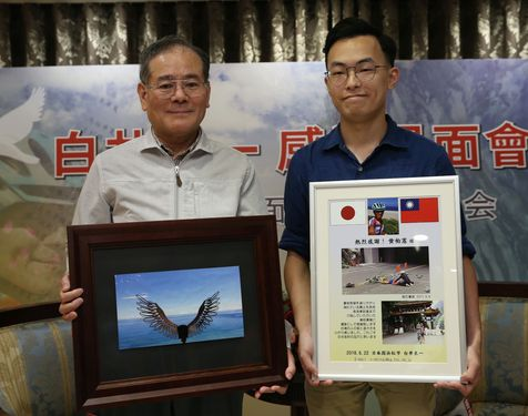 対面会で記念品を交換する白井良一さん(左)と黄柏憲さん