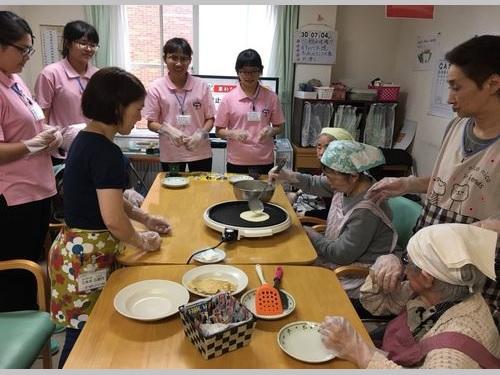 北海道の介護施設で研修を受ける美和科技大学の学生たち(ピンク色のポロシャツの女性)=同大提供