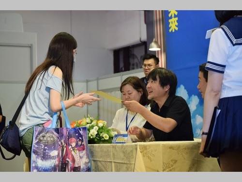 サイン会で台湾の漫画ファンと交流を深める細田守監督(黒いポロシャツの男性)