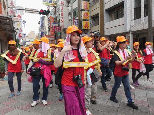 古代中国で使われた首枷を模した道具を身に着けて「城隍夜巡」に参加する人々=嘉義市政府提供