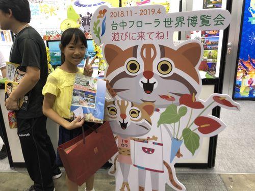 台中花博のキャラクター、タイワンヤマネコの立て看板と記念撮影した子ども=台中市政府提供