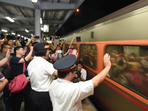 高雄駅の仮設駅で地上を走る列車のラストランを見送る人々