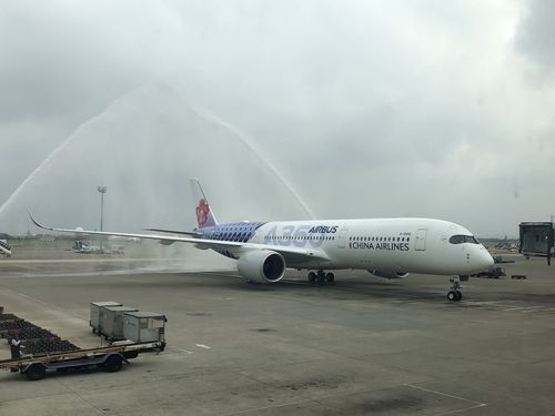 放水アーチで歓迎されるチャイナエアライン・エアバス共同塗装機=23日桃園国際空港で撮影