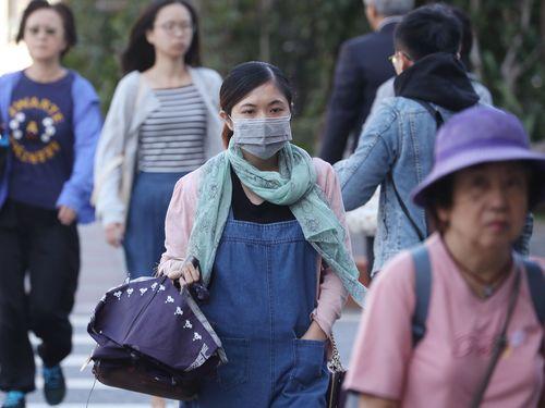 激しい寒暖差に備え、スカーフや帽子を着用する通行人ら