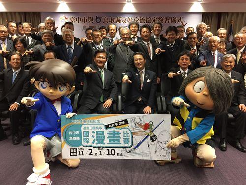 ポーズを決める林佳龍台中市長(プラカードのすぐ後ろの左側の男性)と平井伸治鳥取県知事(同右側)