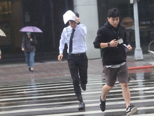 濡れないよう雨の中を走る通行人