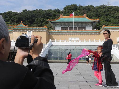 国立故宮博物院・北院を背景に記念撮影をする観光客ら