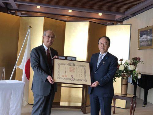 沼田幹夫代表(右)から勲記を手渡される鄭祺耀さん