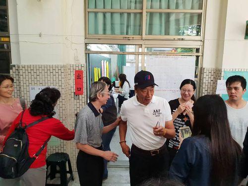 投票所の前に姿を見せる鴻海の郭台銘会長(野球帽をかぶる男性)