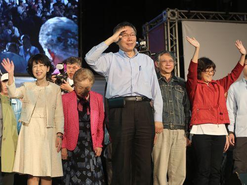 25日未明、再選が決まり集まる支持者たちに敬礼する柯文哲台北市長