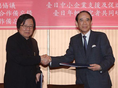 日本台湾交流協会の大橋光夫会長(右)と握手を交わす台湾日本関係協会の邱義仁会長