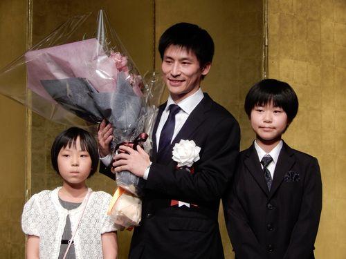 娘たちから花束を贈られた張栩・新名人(中央)