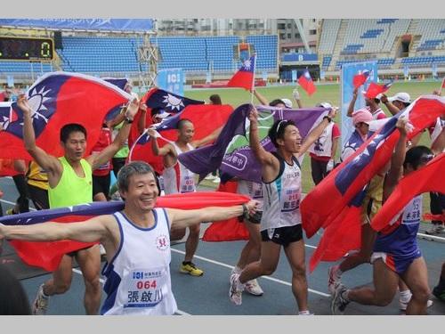 中華民国国旗を掲げながら走る台湾の人々=資料写真