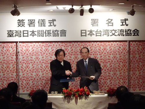 署名式で握手をする(左から)台湾日本関係協会の邱義仁会長と日本台湾交流協会の大橋光夫会長