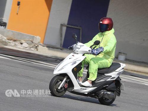 全身を防風衣に包んでスクーターを運転する人=23日撮影