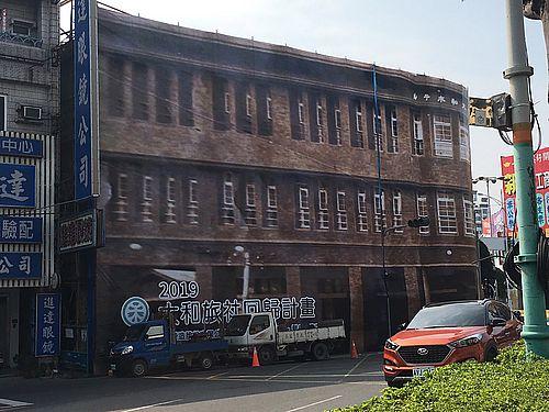 落成当時の姿を描いた大型シートで覆われた旧大和旅社
