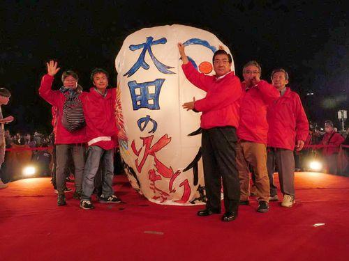 19日夜、新北市平渓で行われた「新北市平渓天灯祭り」で、日本から持ってきた大型の紙風船とともに笑顔を見せる秋田県大仙市の老松博行市長(右3、新北市観光旅遊局提供)