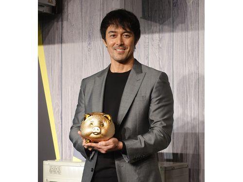 台北市内で20日行われた日系メーカーの新製品発表会で、メーカーから贈呈された「金のブタ」を手に笑顔を見せる阿部寛