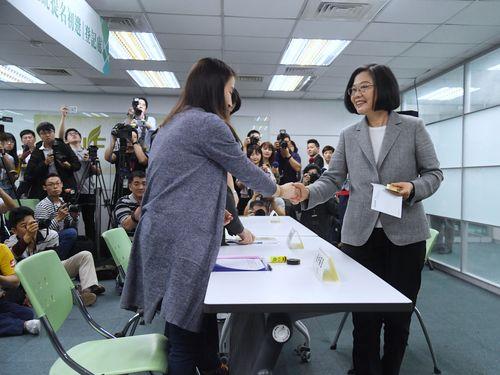 立候補届け出の手続きを終え、党職員と握手を交わす蔡総統(手前右)