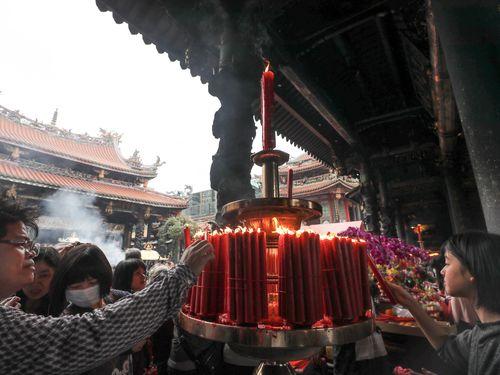 ろうそくをともす龍山寺の参拝客