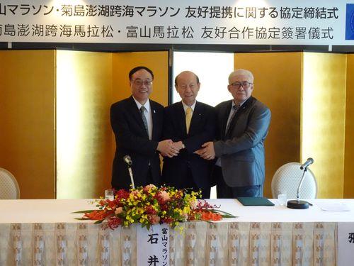 協定締結式で握手を交わす(左から)周永暉観光局長、石井隆一富山県知事、張弘光・澎湖県探索未来発展協会理事長