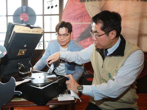 店内に展示されるレコードプレーヤーを操作する黄偉哲台南市長(手前)=同市政府提供