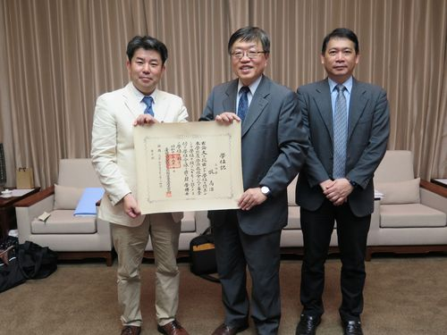 池田真行・富山大副学長(左)から牧高治さんの博士学位記を贈られる陳銘憲・台湾大副学長(中央)=台湾大提供