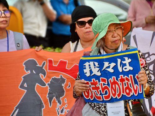「我々はあきらめない」と書かれたプラカードを掲げる陳情活動の参加者
