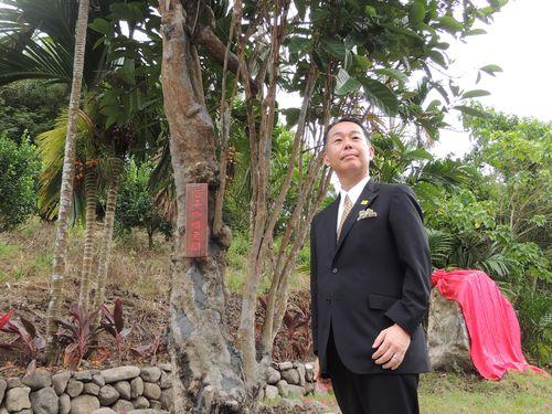 柴田裕氏とコーヒーの木。奥右は赤い布で覆われた記念碑