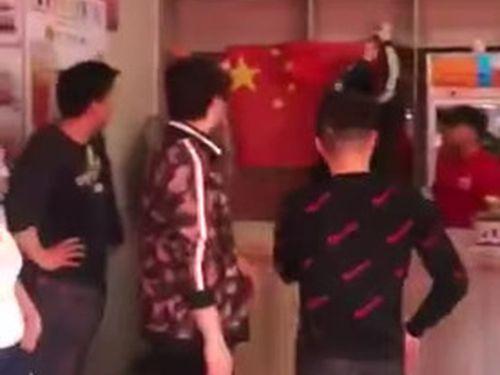 店内に中国の五星紅旗を貼り付ける中国人ら=tony O