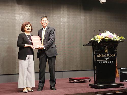 台北市日本工商会の石川理事長(右)から白書を手渡される行政院国家発展委員会の陳主任委員