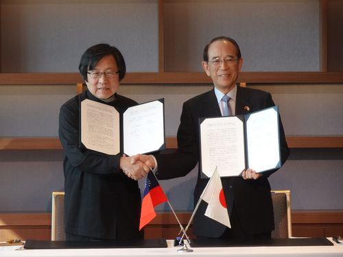 覚書調印式で握手を交わす台湾日本関係協会の邱義仁会長(左)と日本台湾交流協会の大橋光夫会長