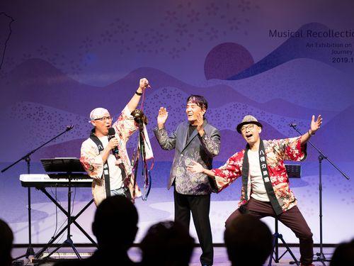 11日の記者会見で歌を披露する日本統治時代生まれのベテラン歌手、林沖さん(中央)と音楽ユニット「八得力楽団」のスタン・リンさん(左)、馬場克樹さん(右)=文化部提供