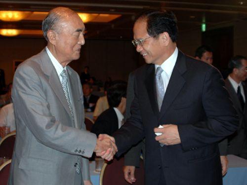 游・総統府秘書長(右)と握手を交わす中曽根元首相=2005年9月、東京