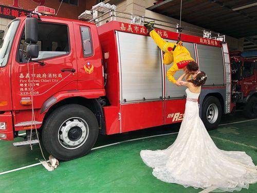 ロープで吊り下げられた消防士が花嫁にキス…ロマンチックな結婚写真